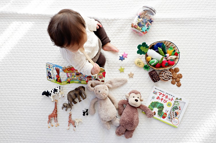 girl sitting among a variety of toys